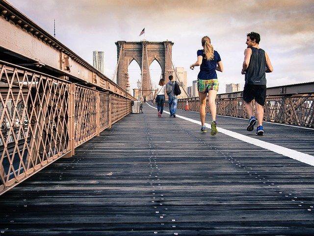 couple running across a bridge